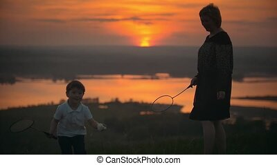 Mother with her little son playing badminton on the hill at sunset