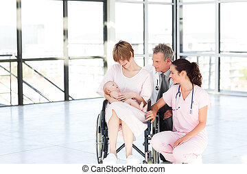 Mother with her newborn baby and doctors with copy-space