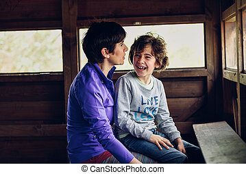 Mother with her seven year old daughter laughing in a cabin...