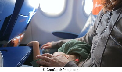 Mother with her sleeping little girl in airplane