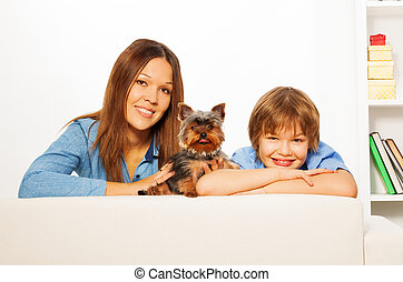 Mother with her son and Yorkshire dog lay on sofa