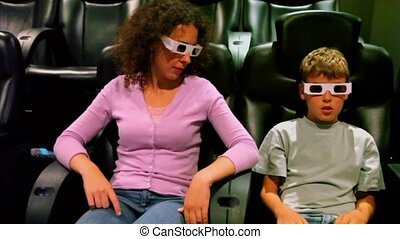 Mother with her son in 3d stereo glasses sit at cinema