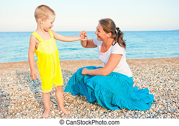 mother with her son on a pebble beach in the evening