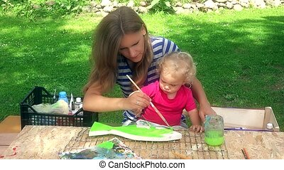 mother with her toddler daughter girl paint wooden fish decoration