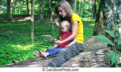 Mother with her toddler daughter using tablet computer sit on fallen tree trunk