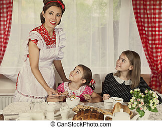Mother with her two daughters have breakfast