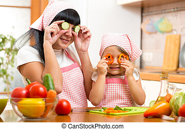 mother with kid preparing healthy food and having fun