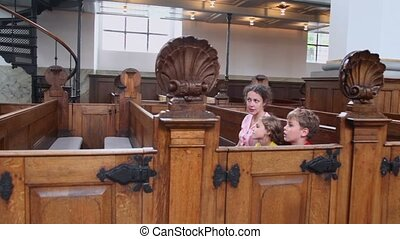 Mother with kids boy and little girl sit at bench in cathedral
