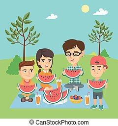Mother with kids eating watermelon at the park.
