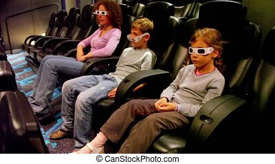Mother with kids in 3d stereo glasses sit at cinema