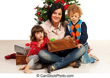 Mother with kids near Xmas tree