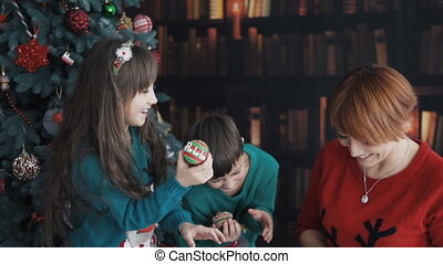 Mother with Kids Playing near Christmas Tree