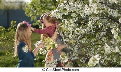 Mother with kids smelling blooming cherry tree