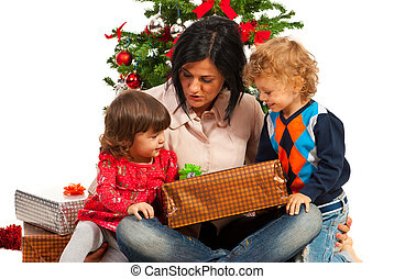 Mother with kids under Christmas tree