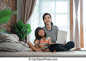 mother with laptop and her child on the bed