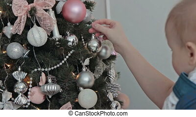 Mother with little boy decorating the Christmas tree
