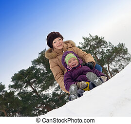 mother with little child sliding in the snow
