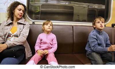 Mother with little daughter and son sit in riding subway train