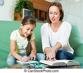 mother with little daughter doing homework together in home...