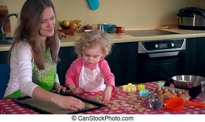 mother with little daughter girl place cookies into oven tin