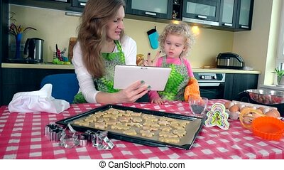 happy mother with little curly daughter bakers looking for recipe on tablet in kitchen. 4K