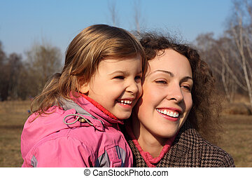 Mother with little daughter on hands outdoor in spring