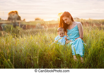 mother with little daughter sitting on meadow