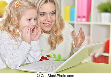 Mother with little daughter using laptop