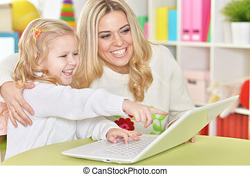 mother with little daughter using modern laptop