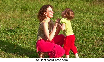 mother with little girl on grass