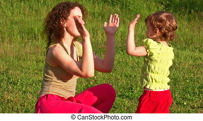 mother with little girl play hands
