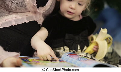Mother with little girl reading a book
