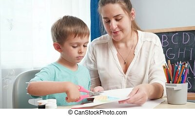 Mother with little son cutting colorful paper while doing homework. Child educating and studying at home during lockdown and self isolation