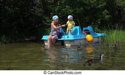 Mother with little son feeding ducks birds sitting on catamaran. Gimbal motion