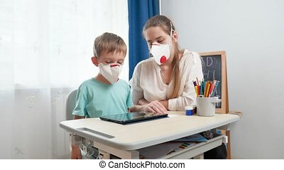 Mother with little son wearing protective medical respirator masks using tablet computer. Doing homework and studying at home during lockdown and self isolation. Remote school concept.