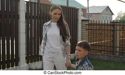 mother with loose dark hair holds adorable little boy hand