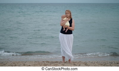 Mother with lost look holding baby being alone at the beach near sea