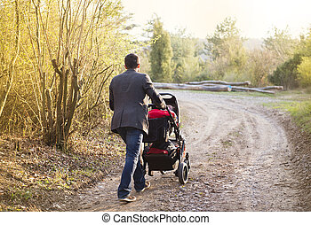 Mother with pram in nature - Happy young father with pram...