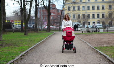 Mother with Pram - mother with baby pram walking through the...