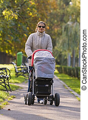 Mother with pram walking in an autumn park.
