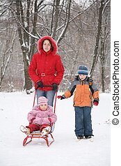 mother with sled and children in park at winter