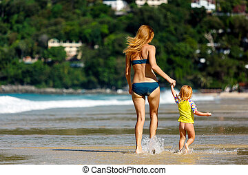 Mother with small baby on the beach