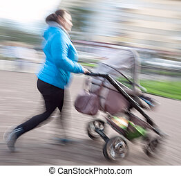 Mother with small children and a pram walking down the...