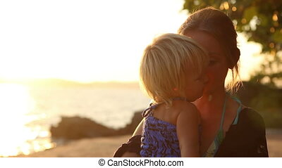 mother with small daughter at sunset against sea