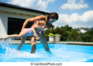 Mother with small daughter in swimming pool outdoors in backyard garden, playing.