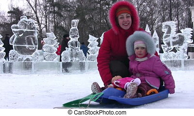Mother with small girl on background of icy figures