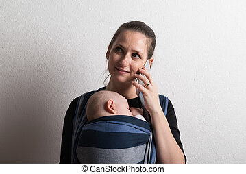Mother with smartphone and baby sleeping in sling. Studio shot.
