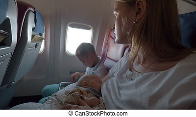 Mother with son and baby daughter flying by plane - Woman...
