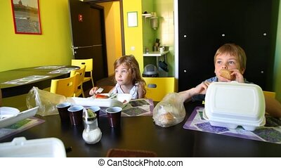 Mother with son and daughter eating at dinning table -...