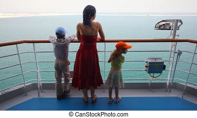 mother with son and daughter stands on deck of cruise ship